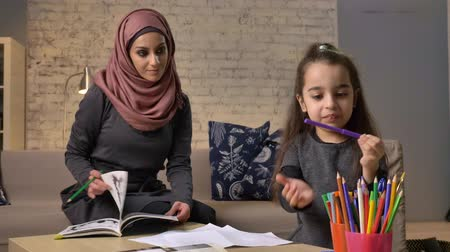 младенчество : A young beautiful mother in a hijab leafing through a book, a little daughter chooses colored pencils, homework, home comfort in the background, colored pencils 50 fps Стоковые видеозаписи