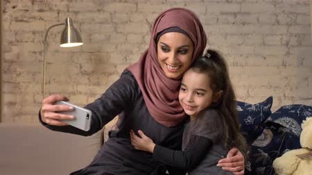 младенчество : Young beautiful mother in hijab with little girl on couch, smiling, uses smartphone, makes selfie, cuddling, little girl with teddy bear, happy family concept home comfort in the background 50 fps