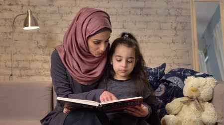 младенчество : Young woman in hijab sits on sofa with her daughter and teaches her how to read, book, happy family concept 50 fps