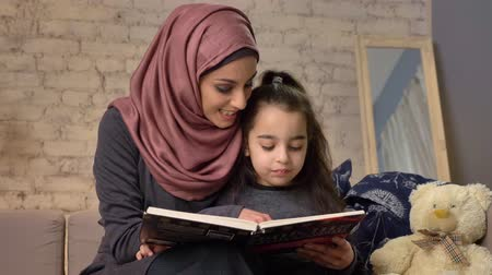 cosiness : Young woman in hijab sits on sofa with her daughter and teaches her how to read, book, happy family concept 50 fps