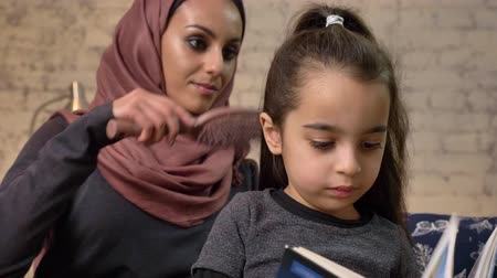 idílio : A young Indian mother wearing a hijab combing hair to her little daughter while child reading a book, sitting on couch, family, home cosiness concept, close up 50 fps