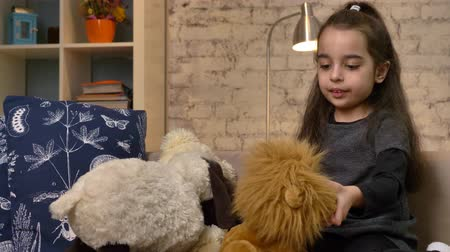 cosiness : A little girl sitting on the couch and playing with a teddy bear and a lion, combs the fur of a toy lion, home comfort in the background 50 fps Stock Footage