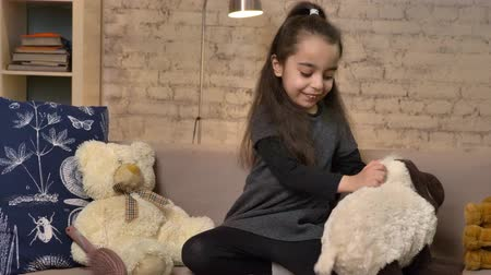 idílio : A little girl sitting on the couch and playing with a teddy sheep, soft toys, home comfort in the background 50 fps Vídeos