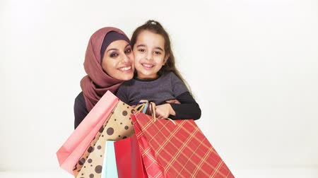 lối sống : Young beautiful mother in hijab hugs her little daughter, holding shopping bags, smiling, happy family on white background, concept 50 fps