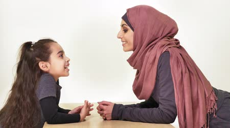 beijos : Young beautiful mother in hijab with her little daughter, look at each other, laughing family, happy family concept, idyll, look at camera 50 fps