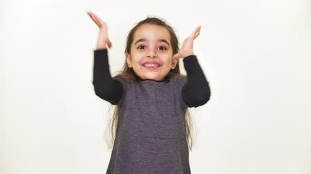 joyfulness : Little beautiful sweet girl is happy, smiling, rejoicing, raises her arms to the top, surprised, white background, white background 50 fps