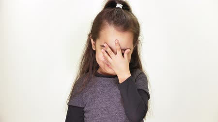 chagrin : Little cute caucasian girl looking at camera, smiling, doing facepalm, showing emotion of disappointment, portrait, white background 50 fps