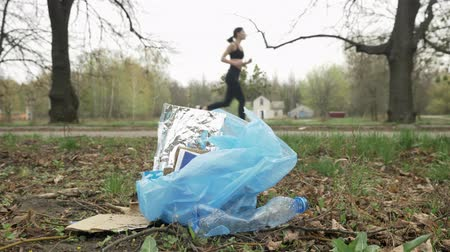 vurguladı : Close-up of garbage in the park, running girl in black suit in the background blurred, plogging concept, 50 fps