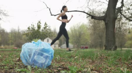 зелень : Close-up of garbage in the park, jogging girl in black suit in the background blurred, plogging concept, 50 fps Стоковые видеозаписи