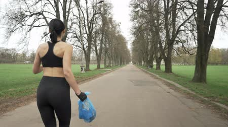 vurguladı : Young athletic girl in a black sport suit runs through green summer park with a trash bag in her hand, plogging concept, back side view 50 fps