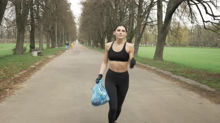 creed : Young athletic girl in a black sport suit and gloves runs through green summer park with a trash bag in her hand, plogging concept, front side view 50 fps Stock Footage