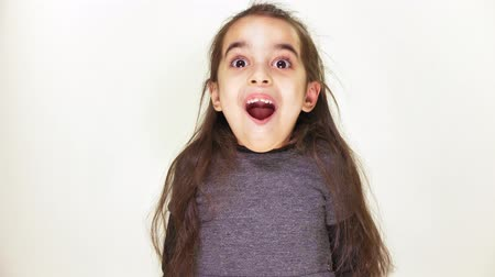 csodálkozás : Little cute caucasian girl, smiling, showing an emotion of surprise, wide-open mouth, portrait white background 50 fps