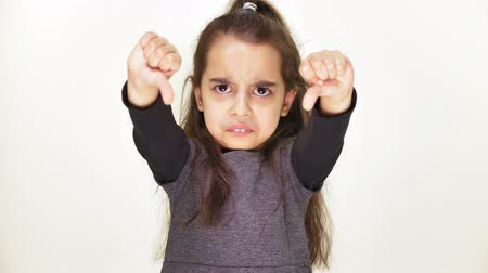 terribly : Little sad little girl showing dislike sign, portrait, white background 50 fps