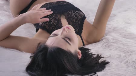 sedução : Young sexy caucasian brunette girl in black lingerie using a smartphone, making selfie lying on the bed, fluffy blanket, white bedroom background close up 50 fps