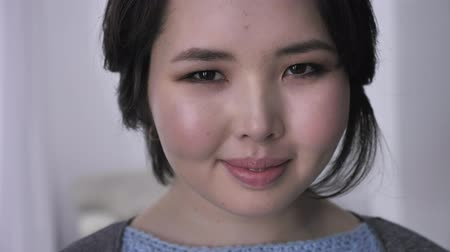 joyfulness : Portrait of young asian brunette girl, looking at camera, serious face, smiling. 50 fps Stock Footage