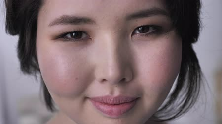 joyfulness : Portrait of young asian brunette girl, looking at camera, serious face, smiling, blinking. 50 fps Stock Footage