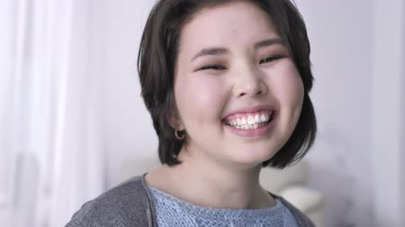 joyfulness : Portrait of young happy asian brunette girl, looking at camera, smiling face, laughing. 50 fps Stock Footage