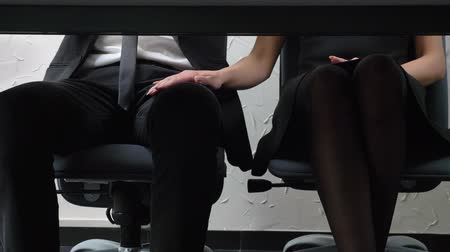 близость : Shot under table, young woman boss sitting beside her employee and touches his leg, flirts, harassment concept 50 fps
