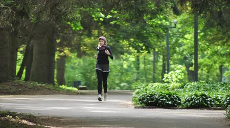 religion health : Young athletic girl in hijab running, jogging in green park, front side view 50 fps Stock Footage