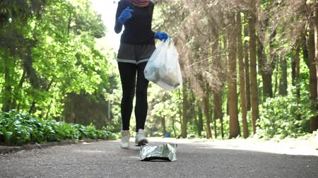 İslamiyet : Plogging concept, young girl in hijab runs through park and cleans up garbage. 50 fps