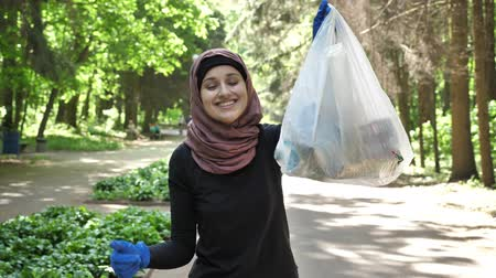 vurguladı : Plogging concept, young girl in hijab runs through park and cleans up garbage, shiwing like sign. 50 fps