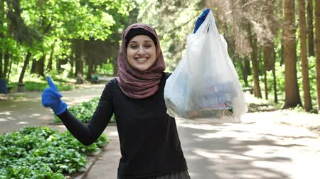 creed : Plogging concept, young girl in hijab runs through park and cleans up garbage, shiwing like sign. 50 fps