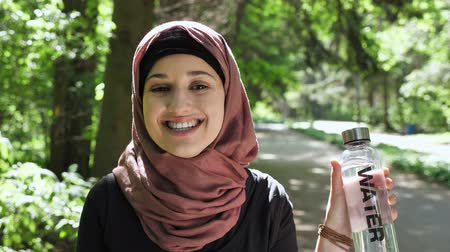 covering : Portrait of a cute young girl in a hijab with a bottle of water in her hands, showing like sign, smiling, looking at the camera, park in the background. 50 fps