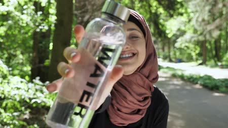 İslamiyet : Portrait of a cute young girl in a hijab with a bottle of water in her hands, smiling, looking at the camera, park in the background, focus pull 50 fps