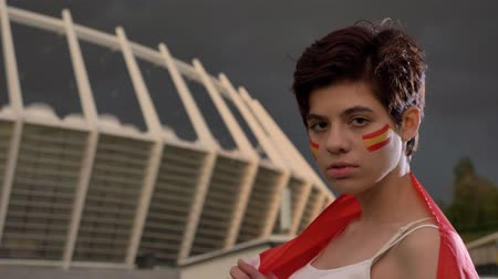graxa : Portrait of a young brunette girl soccer fan in Spain, looking at the camera, serious face, evening stadium in the background 50 fps Vídeos