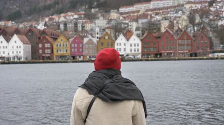 alguns : Silhouette of a man in a red hat standing by the water, colorful houses in the background 50 fps