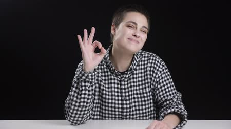 верный : Young short hair girl shows okay sign, smiling, laughing, black background