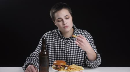 fries : Unusual young girl is eating french fries, burger on plate, bottle of beer on table, diet conception, black background