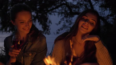 mallow : Two young Caucasian girls sit in the evening by the fire in nature, drink wine, smiling