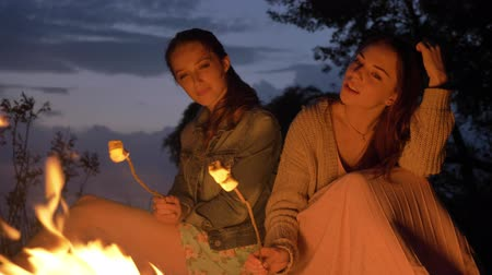 mallow : Two young Caucasian girls sitting by fire in evening in nature, preparing a marshmelow, looking at open fire, thinking