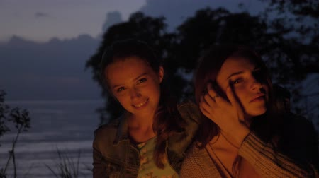 mallow : Two young Caucasian girls sit in the evening by the fire in the nature, looking at the camera, smiling, thinking Stock Footage
