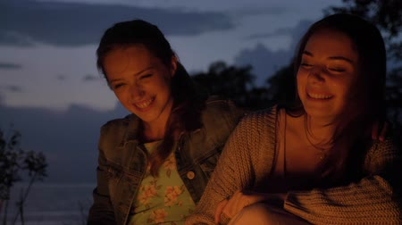 mallow : Two young Caucasian girls sit in the evening by the fire in the nature, laughing, smiling Stock Footage