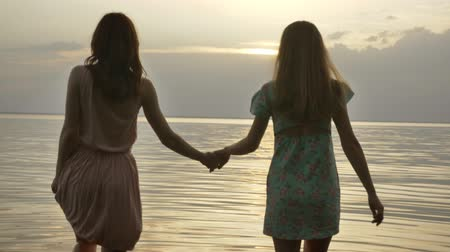 alkony : Two young Caucasian girls in dresses walking in shallow water at sunset