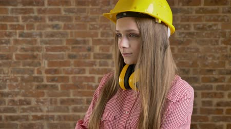 ukłon : Young pretty girl builder nods her head, thinking process, brick background