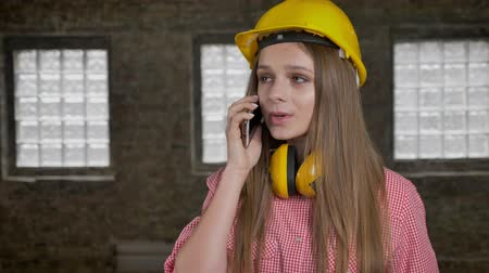 alarmed : Young uptight girl builder is talking on telephone, communication conception Stock Footage