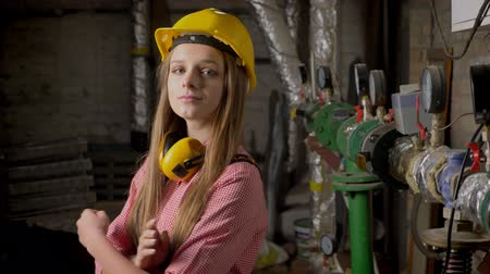 truly : Young cute girl builder is standing near pipes, smiling, crossing arms, watching at camera, building conception Stock Footage