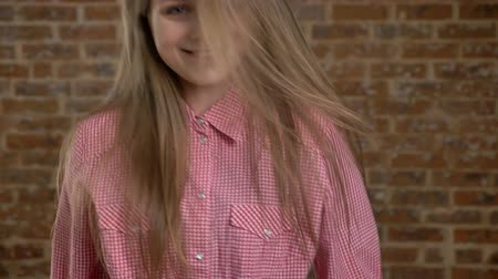 blond vlasy : Young beautiful girl is flipping he hair back, jumping, dancing, watching at camera, brick background Dostupné videozáznamy