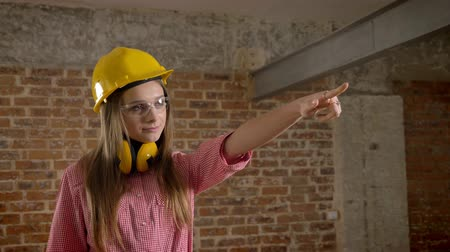 pont : Young confident girl builder points to work and shows thumb up, like sign, brick background