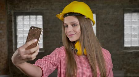 make photo : Young pretty girl builder is taking photos on her smartphone, selfie, communication concept