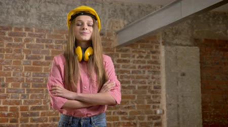 truly : Young pretty girl builder is crossing arms, smiling, watching at camera, brick background