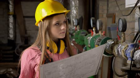 interessado : Young serious girl builder is watching plan of building, thinking