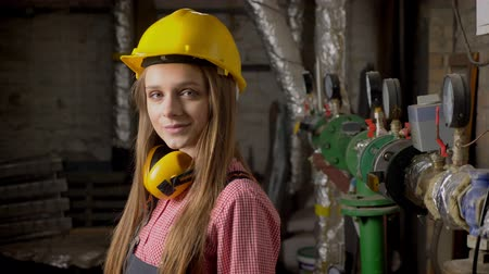 truly : Young cute girl builder is standing near pipes, smiling, watching at camera, building conception Stock Footage