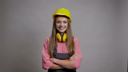 sincerely : Young pretty girl builder is crossing arms, smiling, watching at camera, grey background.