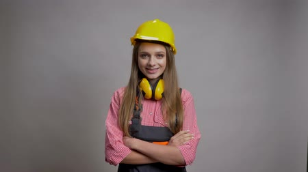 expressar : Young charming girl builder is crossing arms, smiling, watching at camera, grey background Stock Footage