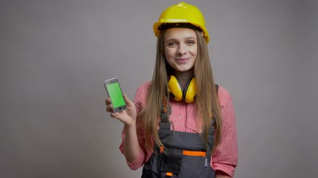 искренний : Young pretty girl builder is showing chroma screen of her phone, smiling, communication concept, grey background