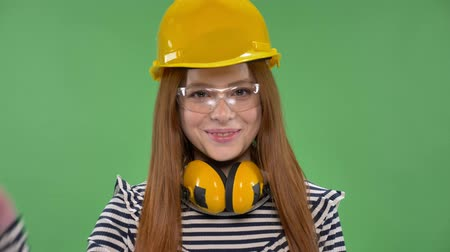 искренний : Young smiling red-haired girl in a construction helmet, headphones, goggles, waving her hand, hello sign